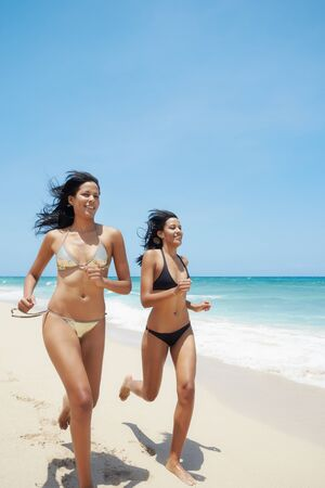 couple of beautiful twins in swimwear running on tropical beach during holidays. Horizontal shape, copy space Stock Photo - 9749790