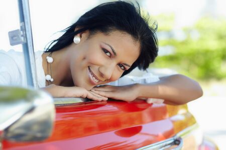 young adult brunette woman leaning on convertible red car and looking at camera. Horizontal shape, side view photo
