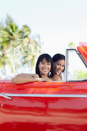 young adult brunette twin women driving convertible red car and looking at camera. Vertical shape, side view, copy space photo