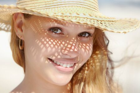 Beautiful happy young woman in straw hat smiling and looking at camera on the beach. Horizontal shape, headshot photo