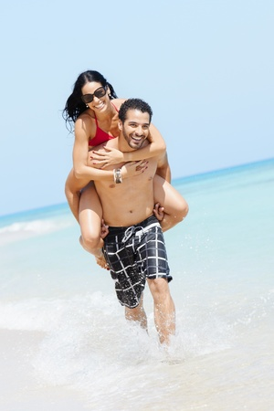 shoulder ride: happy maried adult couple having fun and playing on the sea shore in cuba. Vertical shape, full length, copy space