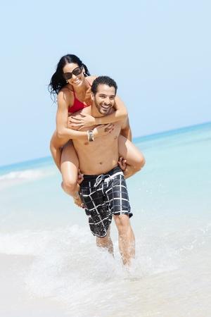 shoulder ride: maried feliz pareja adultos divirti�ndose y jugando en la orilla del mar en cuba. Copiar de forma vertical, larga duraci�n, espacio Foto de archivo