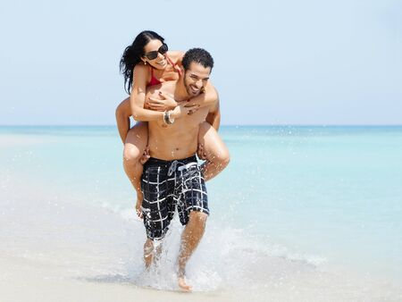 shoulder ride: happy maried adult couple having fun and playing on the sea shore in cuba. Horizontal shape, full length, copy space Stock Photo