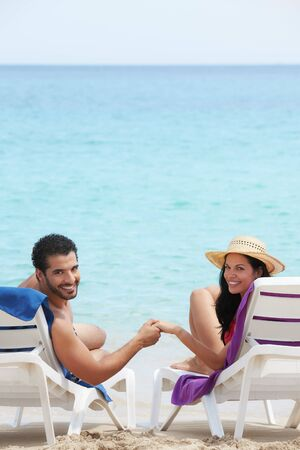 husband and wife relaxing on sunbeds on the beach and smiling at camera. Vertical shape, rear view, copy space photo