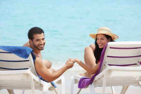 bikini couple: husband and wife relaxing on sunbeds on the beach and smiling at camera. Horizontal shape, rear view, copy space