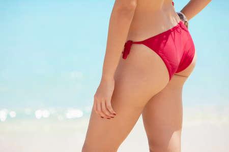 sunbathe: beautiful latin american girl standing on tropical beach with red bikini. Horizontal shape, mid section, copy space Stock Photo