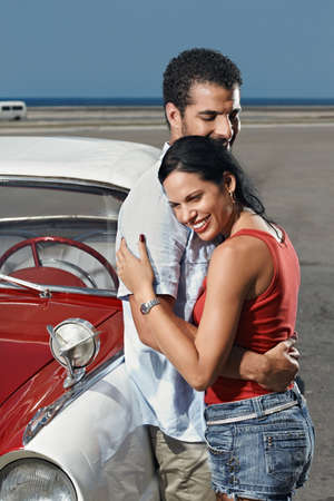 boyfriend and girlfriend leaning on vintage car and hugging in havana, cuba. Vertical shape, side view, copy space photo