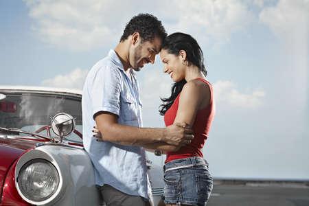 romantic hug: boyfriend and girlfriend leaning on vintage car and hugging in havana, cuba. Horizontal shape, side view, copy space