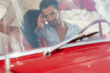 intimate: young happy man and woman dating in red convertible vintage car from the 50s in havana, cuba. Horizontal shape