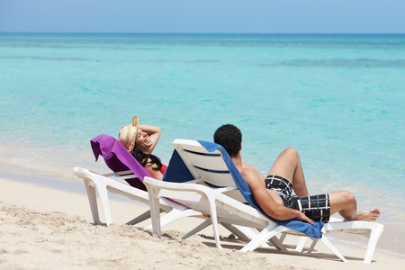 husband and wife relaxing on sunbeds on the beach and smiling. Horizontal shape, side view, copy space photo