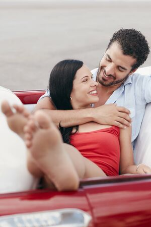 barefoot women: boyfriend and girlfriend lying inside vintage convertible car and hugging. Vertical shape, front view, copy space