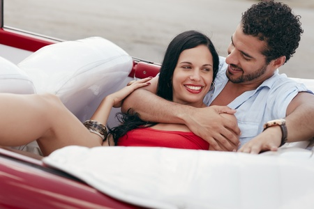 boyfriend and girlfriend lying inside vintage convertible car and hugging. Horizontal shape, side view photo