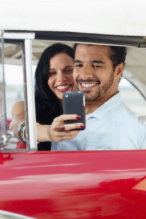 happy young man and woman smiling while taking snapshot with cell phone camera from red vintage convertible car photo
