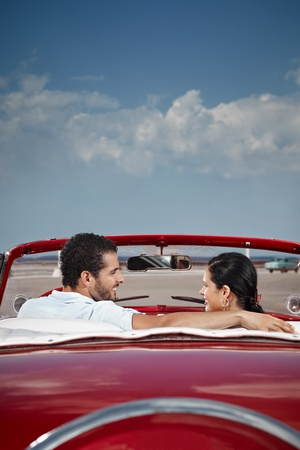 cabriolet: boyfriend and girlfriend sitting in vintage car and hugging in havana, cuba. Vertical shape, rear view, copy space Stock Photo