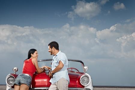 near side: hispanic boyfriend and girlfriend standing near vintage car in havana, cuba. Horizontal shape, side view, copy space