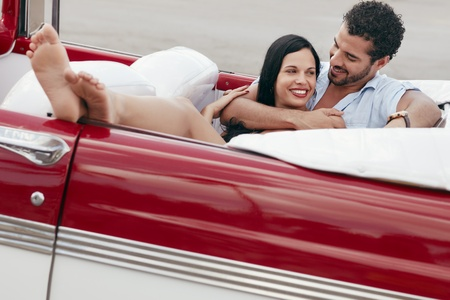 feet crossed: boyfriend and girlfriend lying inside vintage convertible car and hugging. Horizontal shape, full length, side view