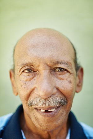 grandfather: portrait of senior hispanic man with dental problems looking at camera against green wall. Vertical shape