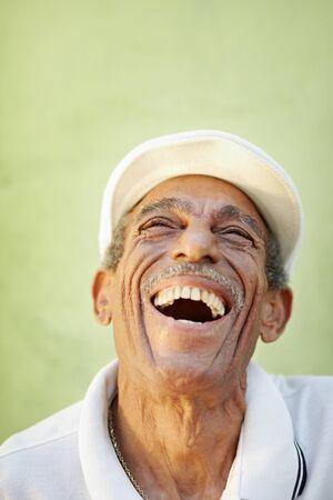 riendo: Retrato de hombre hispano senior con sombrero blanco mirando contra pared verde y sonriente. Forma vertical, espacio de copia