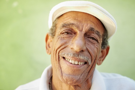 latin look: portrait of senior hispanic man with white hat looking at camera against green wall and smiling. Horizontal shape, copy space