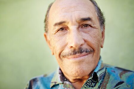 portrait of senior hispanic man with mustache looking at camera against green wall and smiling. Horizontal shape, copy space photo