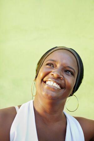 femme regarde en haut: Portrait de femme adulte africaine heureux regardant et souriant. Forme verticale, espace de la copie