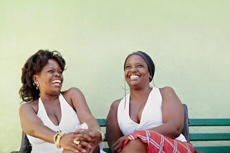 portrait of two happy african adult women talking on bench and smiling. Horizontal shape, copy space photo