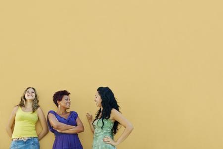 Grupo de tres amigas hispanas apoyándose en pared amarilla y riendo. Forma horizontal, cintura por espacio de copia
