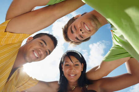 multiethnic group of male and female friends hugging and looking at camera with sky in background. Low angle view photo