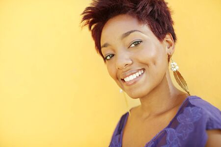 portrait of african college student with earrings smiling at camera with yellow wall in background. Head and shoulders, copy space  photo