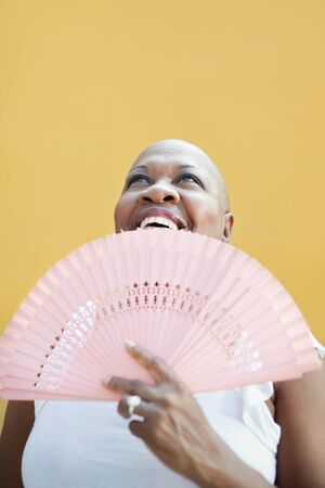 portrait of african 50 years old woman with bald head smiling on yellow background and looking up. Head and shoulders, copy space  photo