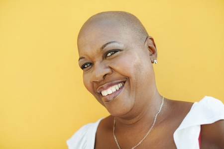 bald head: portrait of african 50 years old woman with bald head smiling at camera on yellow background. Head and shoulders, copy space