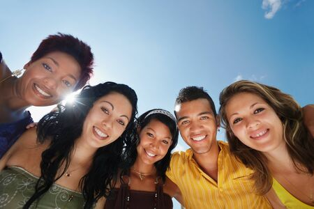 multiethnic group of five male and female friends hugging and looking at camera with sky in background. Low angle view, copy space photo