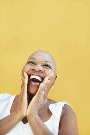 serene people: portrait of african 50 years old surprised woman with bald head, smiling on yellow background. Head and shoulders, copy space