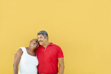 mature latin american couple hugging and smiling with yellow wall in background. Waist up, copy space photo