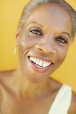portrait of african 50 years old surprised woman with white hair, smiling on yellow background  photo