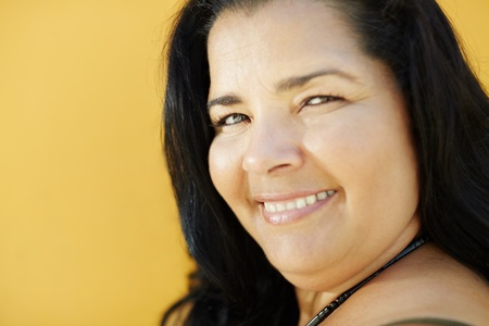 portrait of latin american 50 years old overweight woman smiling on yellow background. Head and shoulders, copy space  photo