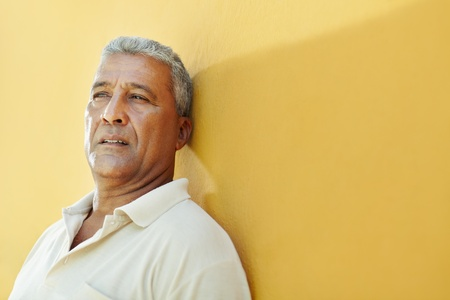 middle aged men: portrait of 50 years old latin american man having problems and leaning on yellow wall. Horizontal shape, copy space