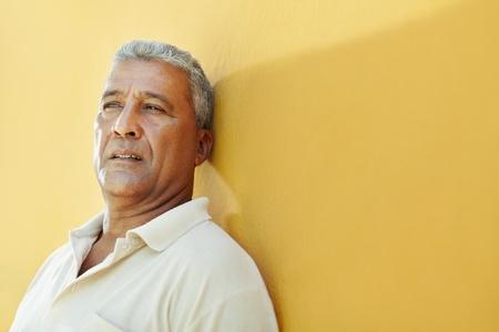 preocupacion: Retrato de hombre latinoamericano de 50 años de edad tiene problemas y apoyándose en pared amarilla. Forma horizontal, espacio de copia