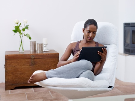 mid adult indian woman relaxing on armchair and using touch pad computer Stock Photo - 10119206