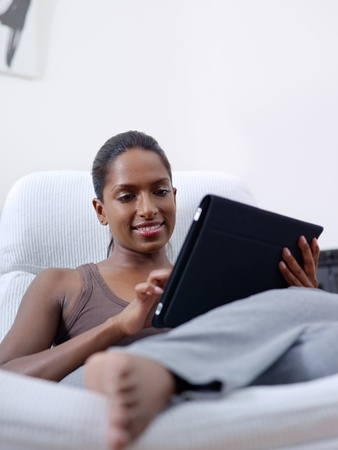 mid adult indian woman relaxing on armchair and using touch pad computer photo