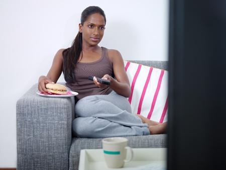 mid adult indian woman on sofa, changing tv channel with remote control and eating junk food Stock Photo