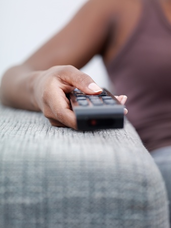changing: closeup of woman on sofa, changing tv channel with remote control. Front view, copy space  Stock Photo