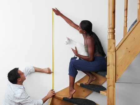 Do it yourself: couple measuring wall to hang picture at home. Horizontal shape, copy space