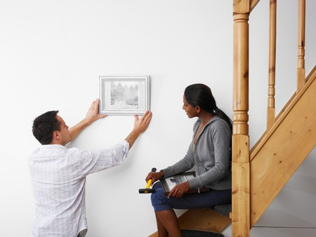 mid adult multiethnic couple hanging pictures to the wall and smiling. Horizontal shape, copy space photo