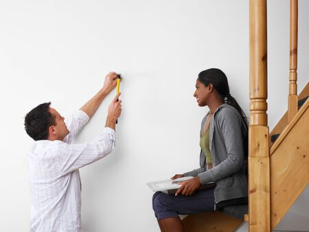 mid adult multiethnic couple using hammer to hang pictures to the wall and smiling. Copy space photo
