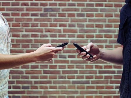young caucasian couple transferring data on mobile phones via bluetooth connection. Copy space Stock Photo - 10161158