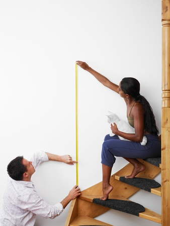 Do it yourself: couple measuring wall to hang picture at home. Vertical shape, copy space photo