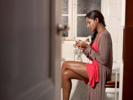 prueba de embarazo: Feliz joven mediante prueba de embarazo en el ba�o. Forma horizontal, espacio de copia