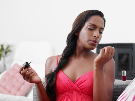 nail varnish: Black woman on sofa, applying nail varnish to her fingernails. Horizontal shape, copy space Stock Photo