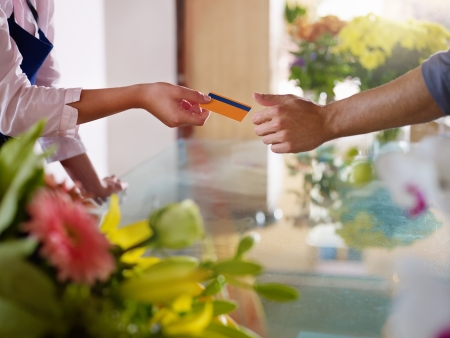 paying: Young woman working as florist giving credit card to customer after purchase. Horizontal shape, closeup